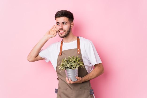 Jonge kaukasische tuinmanmens die een geïsoleerde plant houdt die probeert een roddel te luisteren.