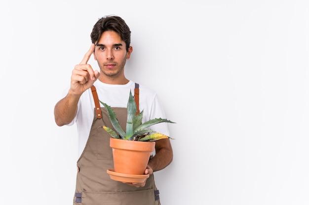 Jonge kaukasische tuinmanmens die een installatie houden die nummer één met vinger tonen.