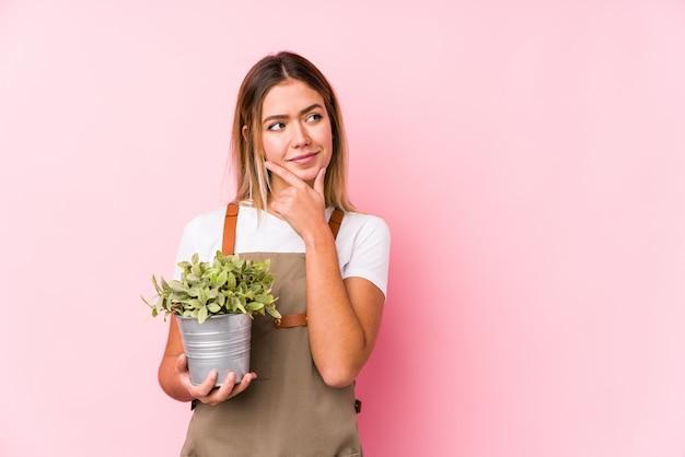 Jonge kaukasische tuinmanvrouw die bij roze zijdelings met twijfelachtige en sceptische uitdrukking kijkt.