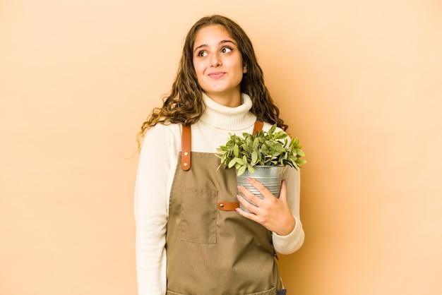 Jonge kaukasische tuinmanvrouw die een geïsoleerde plant houden die dromen van het bereiken van doelstellingen en doeleinden