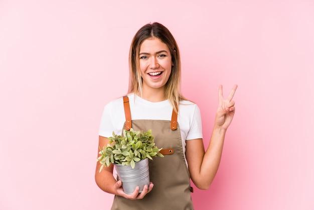 Jonge kaukasische tuinmanvrouw in een roze blij en onbezorgde muur die een vredessymbool met vingers tonen.