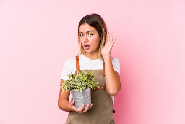 Jonge kaukasische tuinmanvrouw in een roze muur die aan een roddel probeert te luisteren.