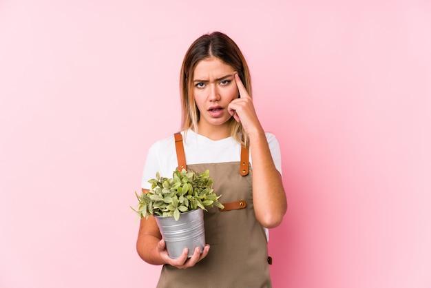 Jonge kaukasische tuinmanvrouw in een roze muur die een teleurstellingsgebaar met wijsvinger tonen.