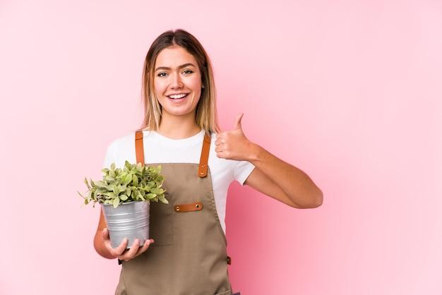 Jonge kaukasische tuinmanvrouw in roze die en duim glimlachen opheffen