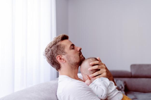 Jonge kaukasische vader die op de borst zijn liefhebbende zoon zittend in de woonkamer op de bank.
