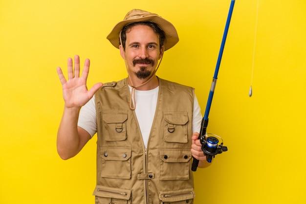 Jonge kaukasische visser die staaf houdt die op gele achtergrond wordt geïsoleerd die vrolijk glimlacht die nummer vijf met vingers toont.