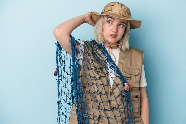Jonge kaukasische vissersvrouw die een net houdt dat op een blauwe achtergrond wordt geïsoleerd en de achterkant van het hoofd aanraakt, denkt en een keuze maakt.