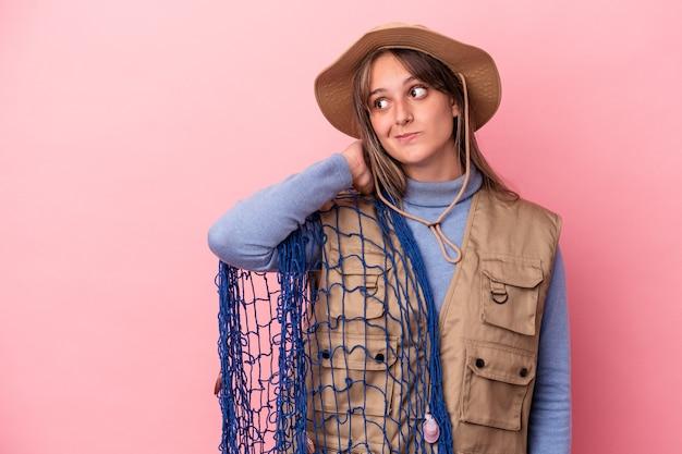 Jonge kaukasische vissersvrouw die een net houdt dat op een roze achtergrond wordt geïsoleerd en de achterkant van het hoofd aanraakt, denkt en een keuze maakt.