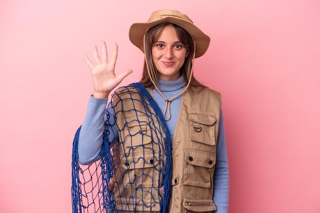 Jonge kaukasische vissersvrouw die een net houdt dat op roze achtergrond wordt geïsoleerd glimlachend vrolijk die nummer vijf met vingers toont.