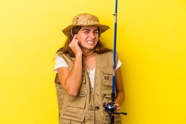 Jonge kaukasische vissersvrouw die een staaf houdt die op gele achtergrond wordt geïsoleerd die oren behandelt met handen.