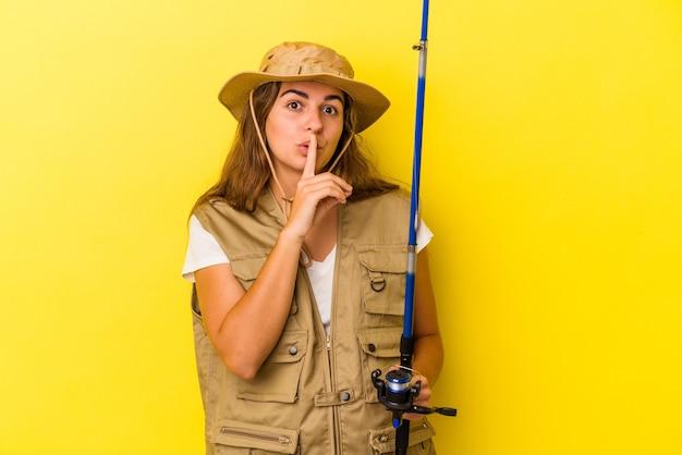 Jonge kaukasische vissersvrouw die een staaf houdt die op gele achtergrond wordt geïsoleerd en een geheim houdt of om stilte vraagt.