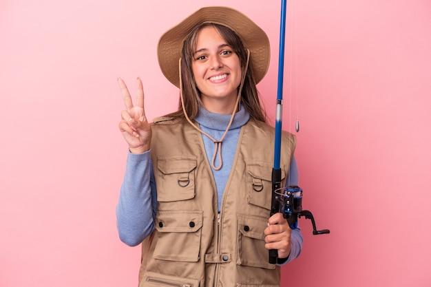 Jonge kaukasische vissersvrouw die een staaf houdt die op roze achtergrond wordt geïsoleerd die nummer twee met vingers toont.