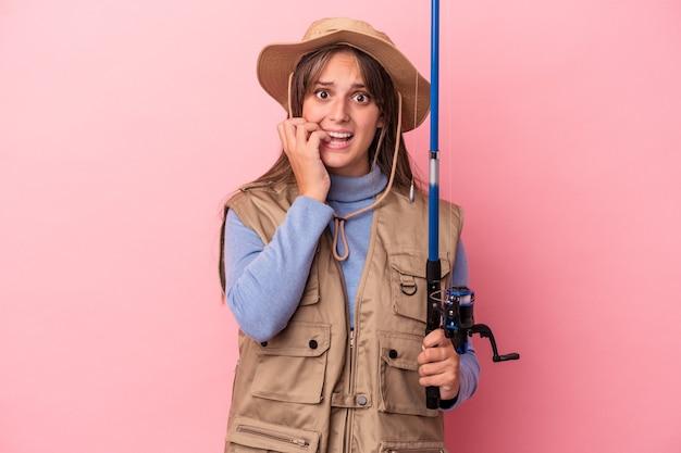 Jonge kaukasische vissersvrouw die een staaf houdt die op roze achtergrond wordt geïsoleerd en vingernagels bijt, nerveus en erg angstig.