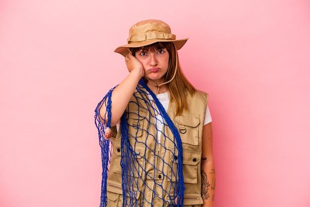 Jonge kaukasische vissersvrouw die net geïsoleerd op een blauwe achtergrond vasthoudt, geschokt is, herinnert ze zich een belangrijke vergadering.