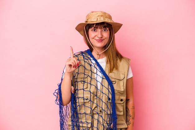 Jonge kaukasische vissersvrouw die net houdt dat op blauwe achtergrond wordt geïsoleerd die nummer één met vinger toont.