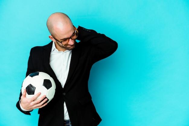 Jonge kaukasische voetbaltrainer die op witte achtergrond wordt geïsoleerd die achterkant van het hoofd raakt, denkt en een keuze maakt.