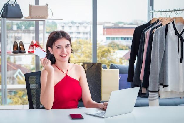 Jonge kaukasische vriendelijke vrouw die met laptop werkt en online elektronische handel verkoopt die bij kleren winkelt.