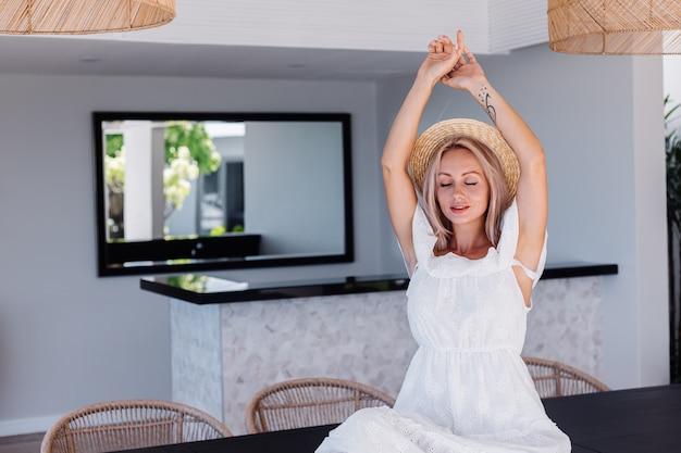 Jonge kaukasische vrij blonde haarvrouw in openluchtkeuken bij villa