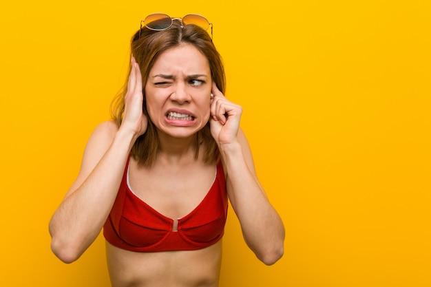 Jonge kaukasische vrouw bikini dragen en zonnebril die haar oren behandelen met haar handen.