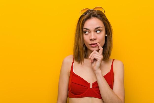 Jonge kaukasische vrouw bikini dragen en zonnebril die zijdelings met twijfelachtige en sceptische uitdrukking kijken.