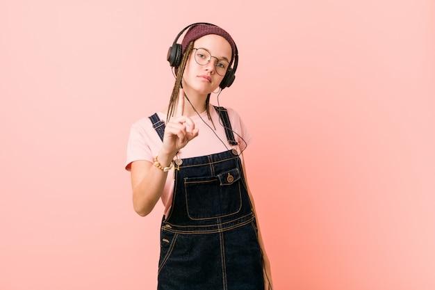 Jonge kaukasische vrouw die aan muziek luistert die nummer één met vinger toont.