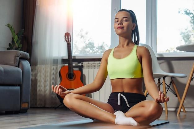 Jonge kaukasische vrouw die ademhalingsoefening op yogamat thuis maken
