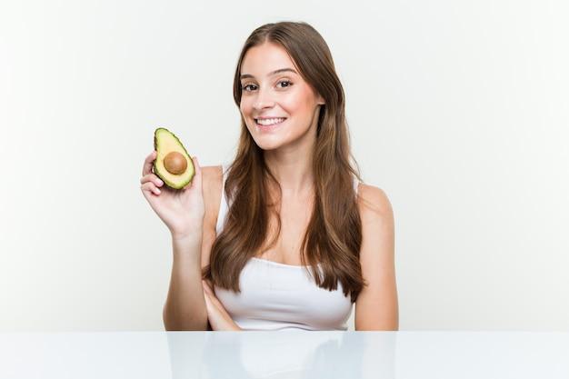 Jonge kaukasische vrouw die avocado glimlachen houden zeker met gekruiste wapens.