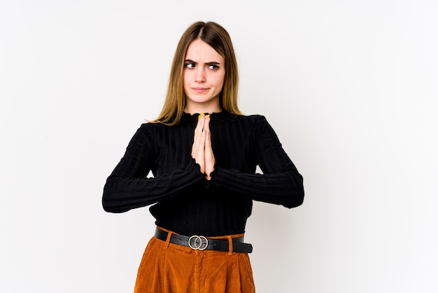 Jonge kaukasische vrouw die bij het witte bidden wordt geïsoleerd, die toewijding toont, godsdienstige persoon die goddelijke inspiratie zoekt.