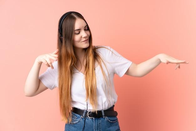 Jonge kaukasische vrouw die bij roze muur het luisteren muziek en het dansen wordt geïsoleerd