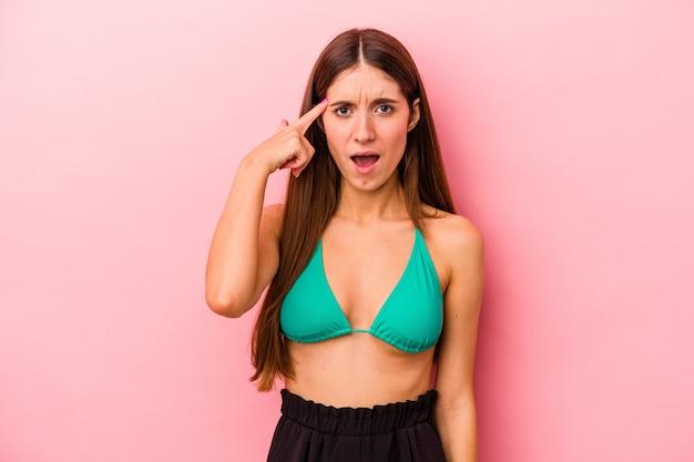 Jonge kaukasische vrouw die bikini draagt die op roze achtergrond wordt geïsoleerd die een teleurstellingsgebaar met wijsvinger toont.