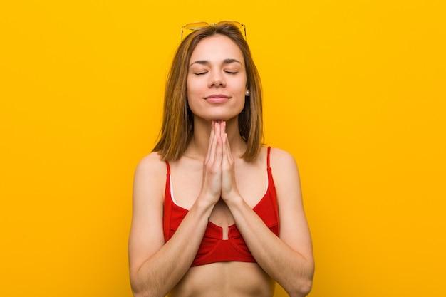Jonge kaukasische vrouw die bikini en zonnebril hand in hand bidt dichtbij mond draagt, voelt zich zelfverzekerd.