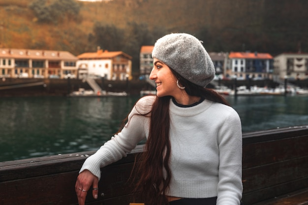 Jonge kaukasische vrouw die de baai van pasaia bekijkt in baskenland.