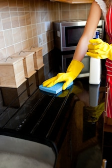 Jonge kaukasische vrouw die de oven schoonmaakt