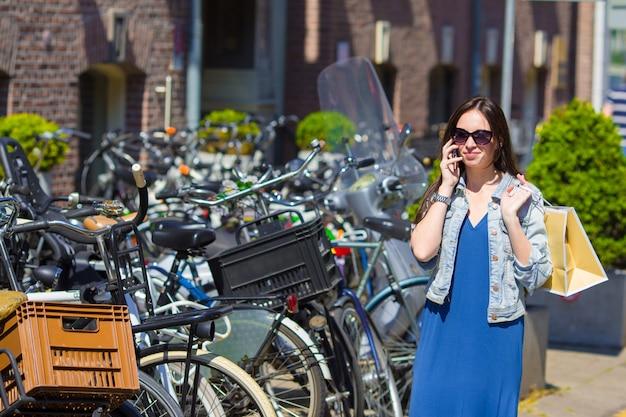 Jonge kaukasische vrouw die door celtelefoon spreekt in europese stad