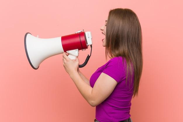 Jonge kaukasische vrouw die door een megafoon spreekt