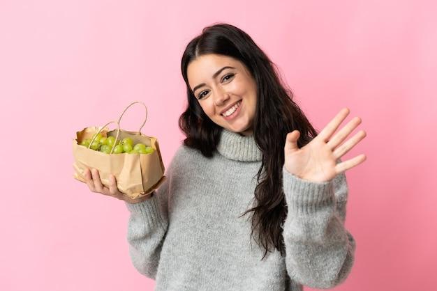 Jonge kaukasische vrouw die druiven geïsoleerd houden die met hand met gelukkige uitdrukking groeten