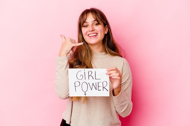 Jonge kaukasische vrouw die een aanplakbiljet van de meisjesmacht houdt dat op roze wordt geïsoleerd dat een gsm-gebaar met vingers toont.