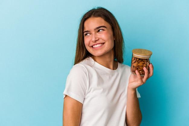 Jonge kaukasische vrouw die een amandelkruik houdt die op blauwe achtergrond wordt geïsoleerd kijkt opzij glimlachend, vrolijk en prettig.