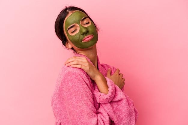 Jonge kaukasische vrouw die een badjas en een gezichtsmasker draagt dat op roze achtergrond wordt geïsoleerd