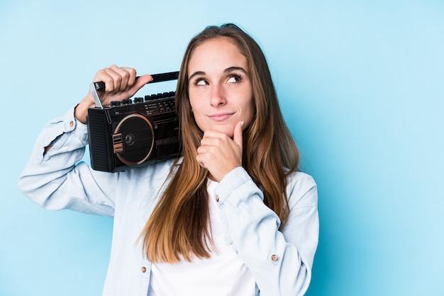 Jonge kaukasische vrouw die een cassete houdt kijkend zijdelings met twijfelachtige en sceptische uitdrukking.