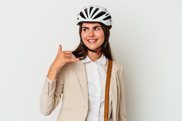 Jonge kaukasische vrouw die een fiets berijdt om te werken die op witte achtergrond wordt geïsoleerd die een mobiel telefoongesprekgebaar met vingers toont.