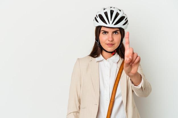 Jonge kaukasische vrouw die een fiets berijdt om te werken die op witte achtergrond wordt geïsoleerd die nummer één met vinger toont.