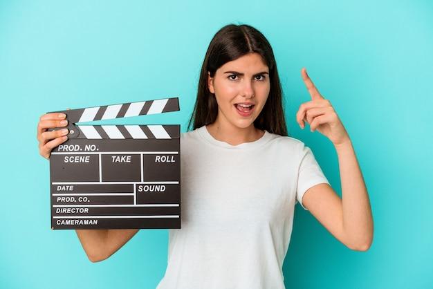 Jonge kaukasische vrouw die een filmklapper houdt die op blauwe achtergrond wordt geïsoleerd die een idee, inspiratieconcept heeft.