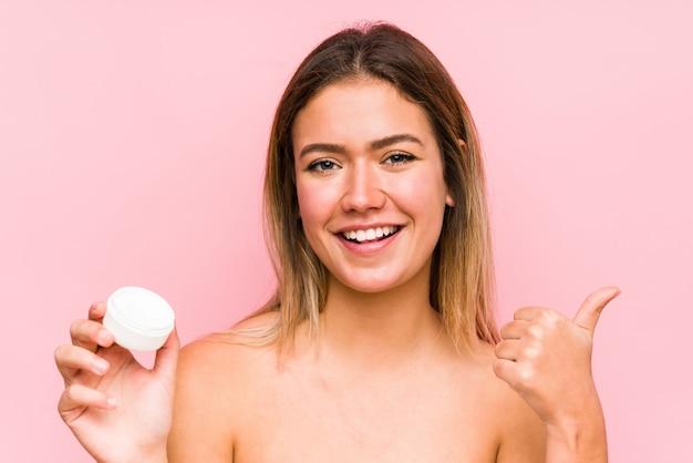 Jonge kaukasische vrouw die een geïsoleerd vochtinbrengende crème houdt en duim opheft