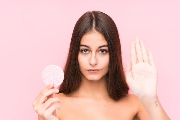 Jonge kaukasische vrouw die een geïsoleerde gezichtsschijf houdt die zich met uitgestrekte hand bevindt die stopbord toont, dat u verhindert.