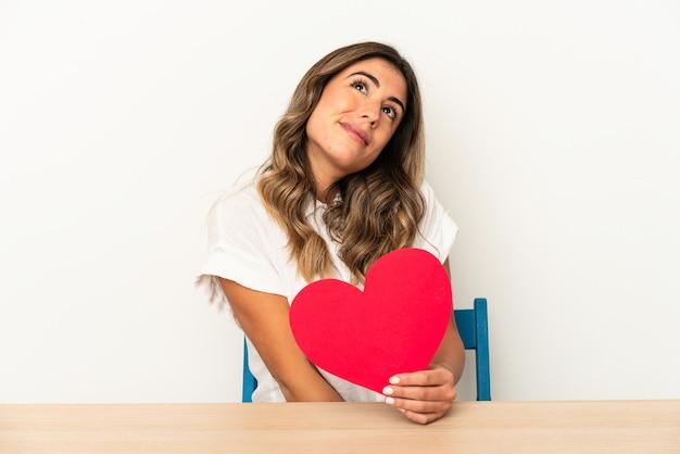 Jonge kaukasische vrouw die een geïsoleerde hart van de valentijnskaartendag houdt dromen van het bereiken van doelstellingen en doeleinden