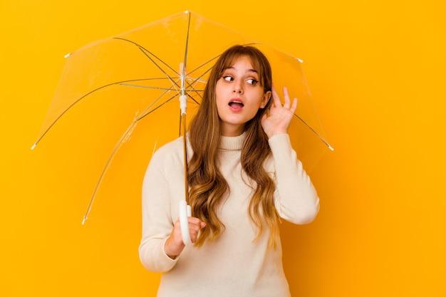 Jonge kaukasische vrouw die een geïsoleerde paraplu houdt die een roddel probeert te luisteren.