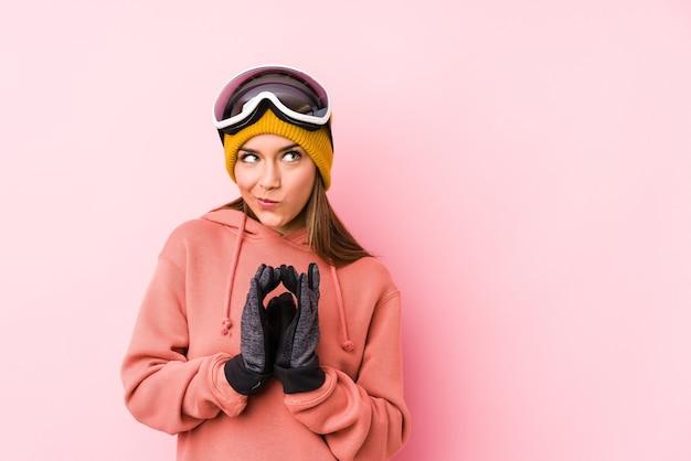 Jonge kaukasische vrouw die een geïsoleerde skikleren draagt die plan in mening verzint, een idee opzet.