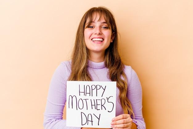 Jonge kaukasische vrouw die een gelukkig aanplakbiljet van de moedersdag houdt dat en pret lacht heeft