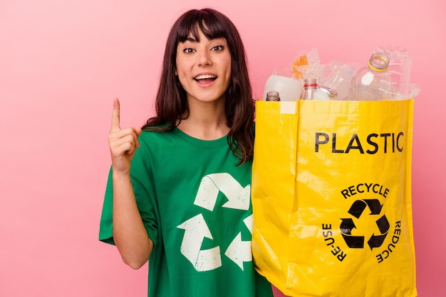 Jonge kaukasische vrouw die een gerecycleerde plastic zak houdt die op roze achtergrond wordt geïsoleerd die een idee, inspiratieconcept heeft.
